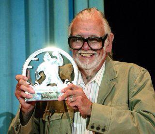 George Romero luciendo uno de los trofeos realizados por Joordu.