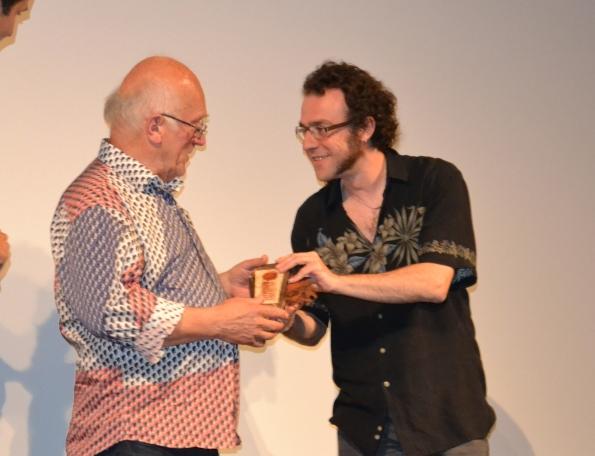 Colin recibiendo su Sierra Circular Honorífica de manos del director del certamen.